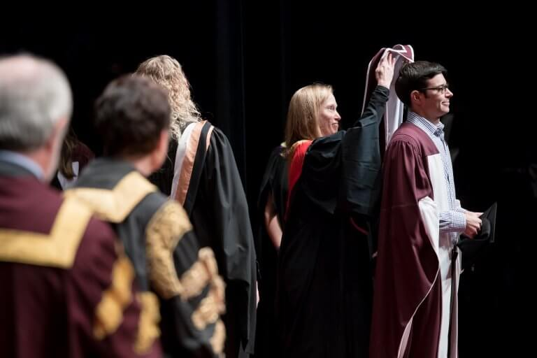 Student receiving hood on stage at convocation