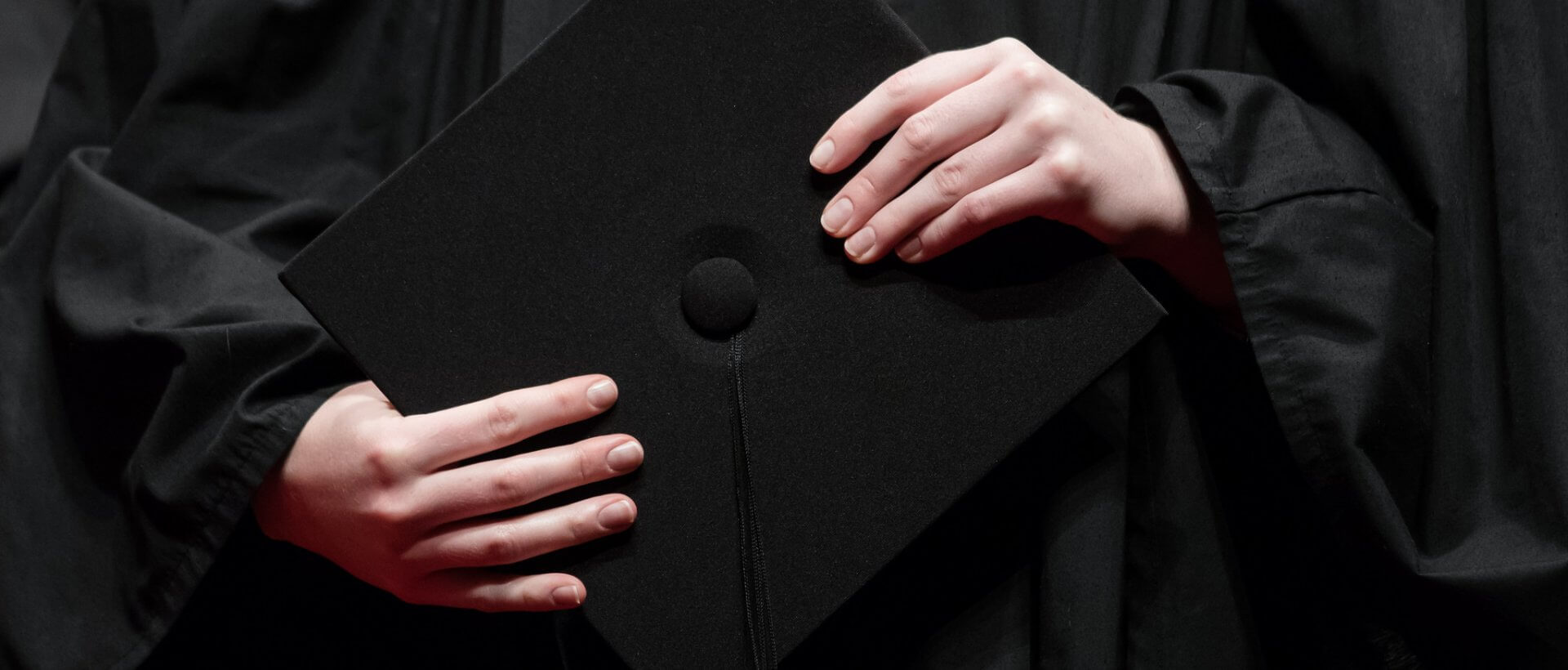 Person holding their grad cap