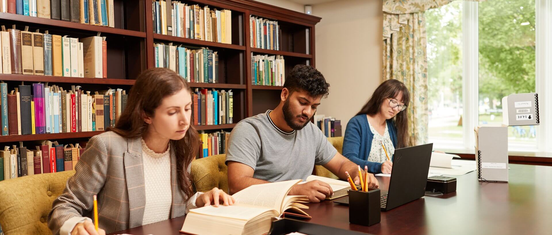 Three students studying in a library