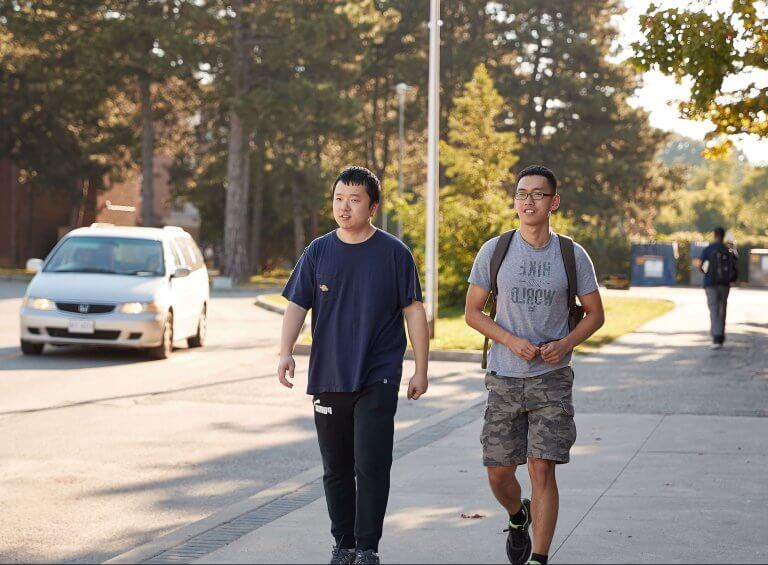Two students on the sidewalk walking to campus