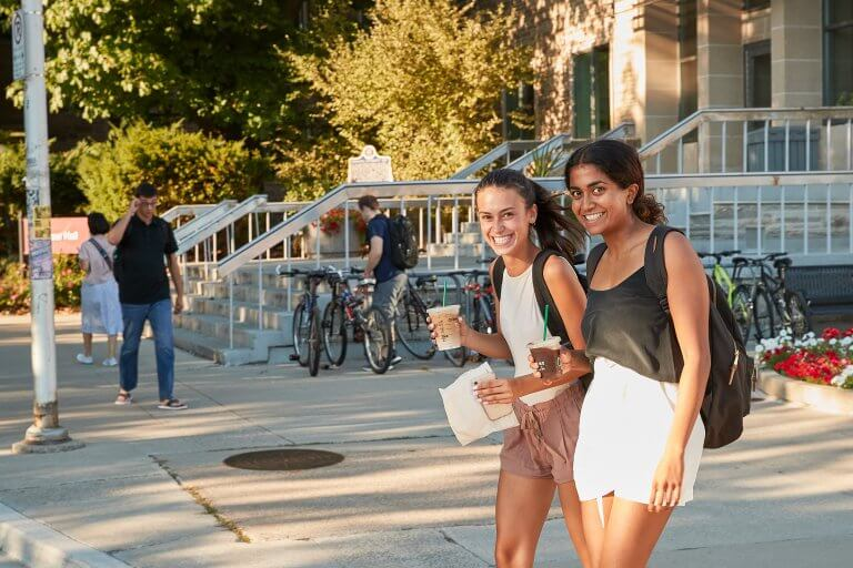 Two students walking by Gilmour Hall in the evening sun