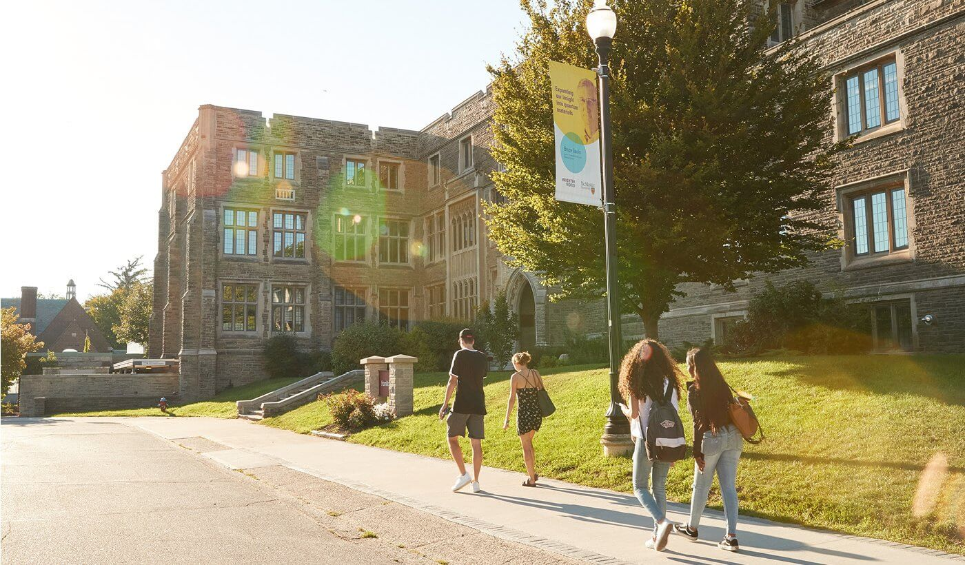 Four students walking towards campus in the summer